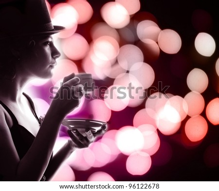 A woman with a cup of coffee on a background of night lights.
