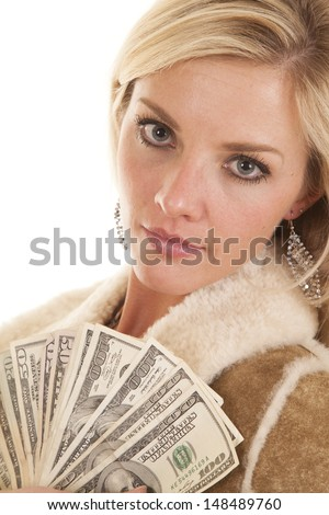 A woman with a fan of money looking.