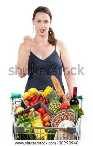 A woman with a full shopping cart happy to be shopping - punching the air on a white background.
