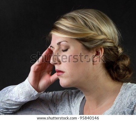A woman with a headache against a dark background