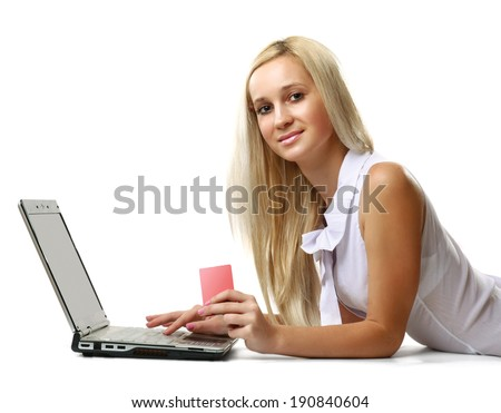 A woman with a laptop and a credit card, lying on the floor, isolated on white - stock photo