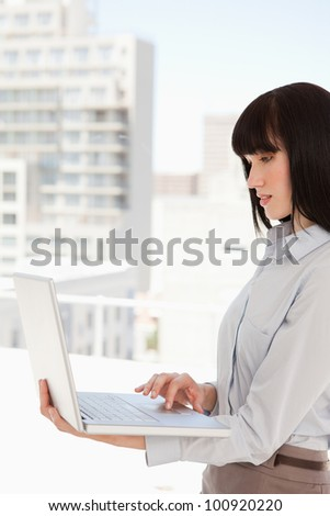 A woman with a laptop in her hand uses it while at work - stock photo