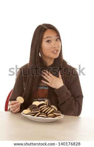 A woman with a plate of cookies on the table not wanting to share. - stock photo