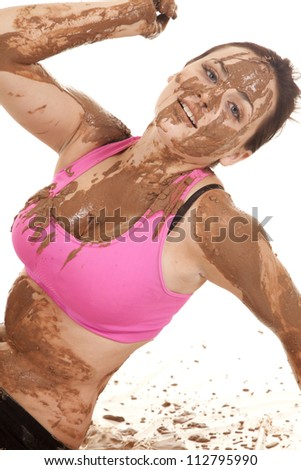 A woman with a playful expression on her face covered in mud - stock photo