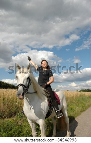 A woman with a raised hand sits on Andalusian horse.
