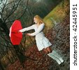 A woman with a red umbrella in autumn park - stock photo