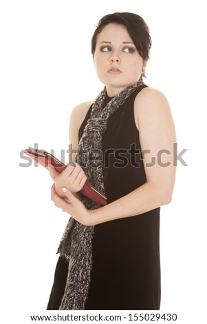 A woman with a scared expression on her face looking over her shoulder holding onto her tablet - stock photo