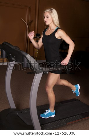 A woman with a serious expression and running on her treadmill. - stock photo