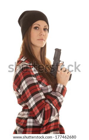 a woman with a serious expression on her face holding on to a pistol. - stock photo