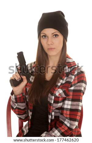 a woman with a serious expression on her face holding on to her gun. - stock photo