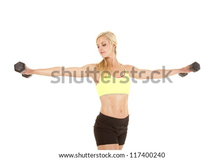 A woman with a serious expression on her face holding out weights in a fly motion.