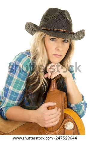a woman with a serious expression on her face, in her blue plaid shirt, and her cowgirl hat, leaning on her saddle. - stock photo