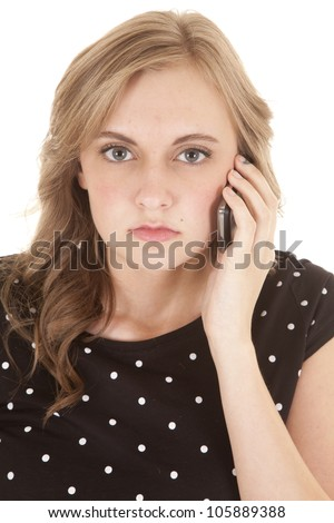 A woman with a serious expression on her face with her cell phone up to her ear. - stock photo