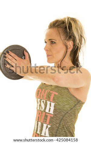 A woman with a serious expression on her face, working on her chest muscles with a weight. - stock photo