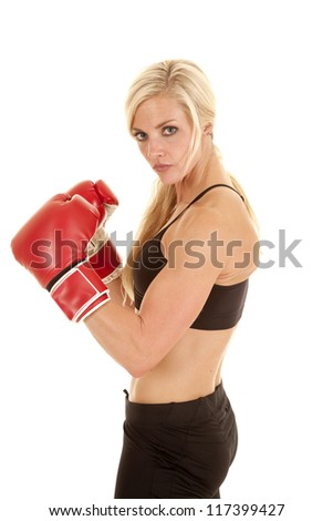 a woman with a serious expression wearing boxing gloves.