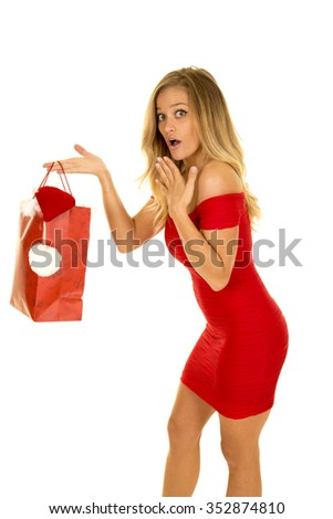 A woman with a shocked expression holding out her Christmas bag.