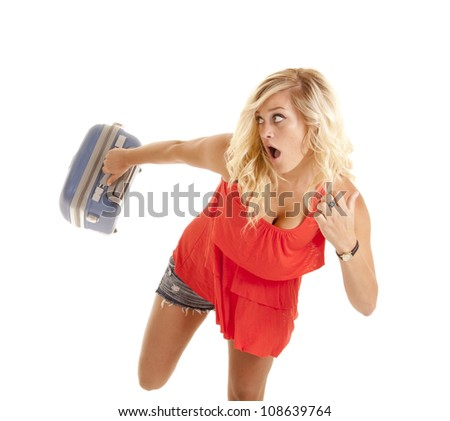 a woman with a shocked expression running with her suitcase because she is late. - stock photo