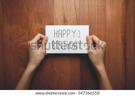 a woman with a sign in her hands with the words happy birthday - stock photo