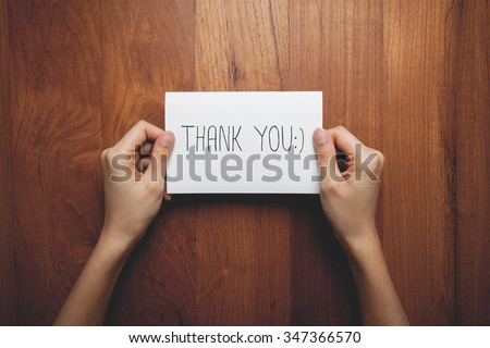 a woman with a sign in her hands with the words thank you - stock photo