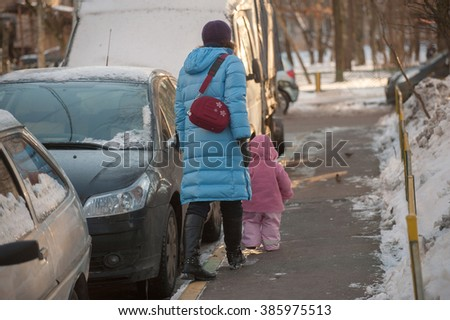 A woman with a small child go away down the sidewalk near a snow-covered cars in winter.