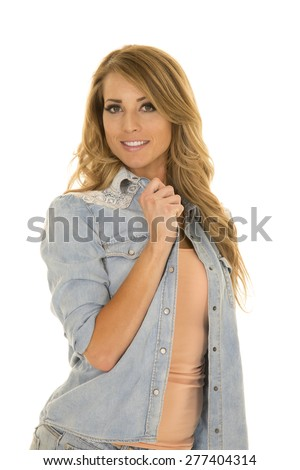 A woman with a smile on her face, holding on to her collar. - stock photo