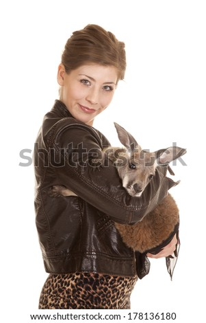 a woman with a smile on her face holding on to her pet kangaroo. - stock photo
