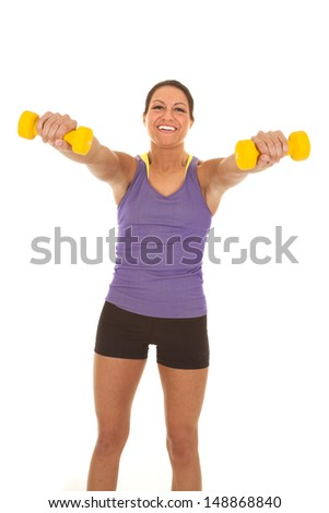 A woman with a smile on her face, holding out her weights.