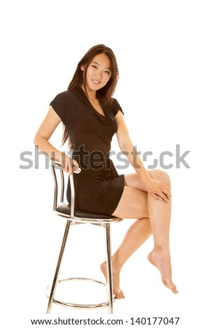 A woman with a smile on her face in her black dress sitting on a stool
