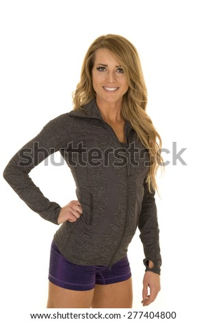 A woman with a smile on her face, in her tight jacket and shorts. - stock photo
