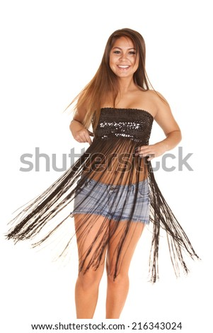 a woman with a smile on her face, twirling around and letting the fringe on her dress flow. - stock photo