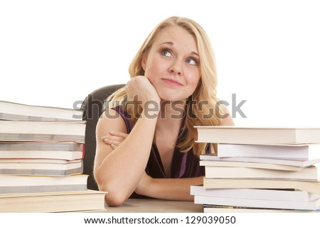 a woman with a smile on her face while sitting at her desk looking up - stock photo