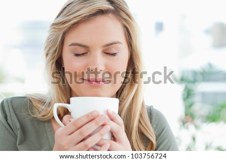 A woman with a soft smile and closed eyes, smelling the aroma from her cup in front of her.