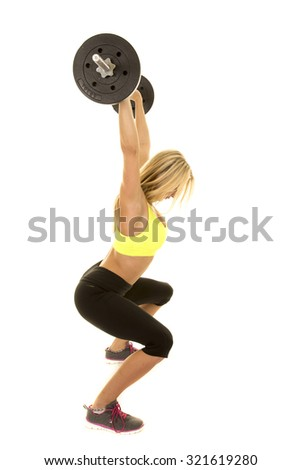 a woman with a weight above his head doing a squat. - stock photo