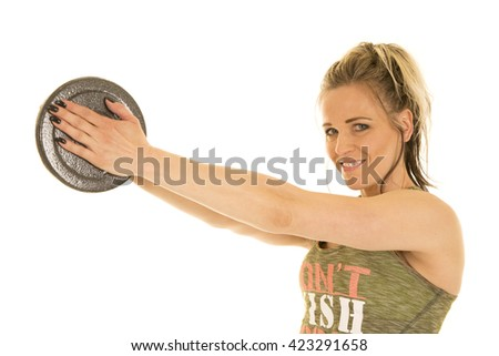 A woman with a weight holding it out in front of her with a smile. - stock photo