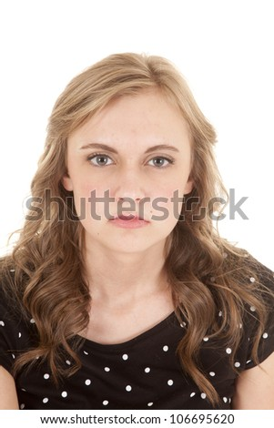 A woman with an unhappy expression on her face in her black and white polka dot shirt on. - stock photo