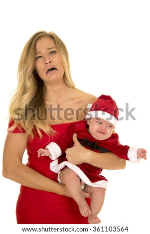 A woman with an upset expression on her face holding her crying baby, in her santa outfit.