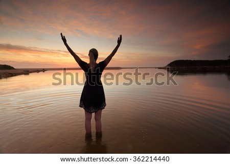 A woman with arms outstretched towards the sky in an act of success, praise of mother nature, or  worship of spirituality or religion on an amazing sunrise morning.  Dee Why Lagoon, Australia - stock photo
