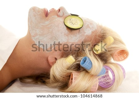 A woman with curlers in her hair and a face mask with cucumbers. - stock photo