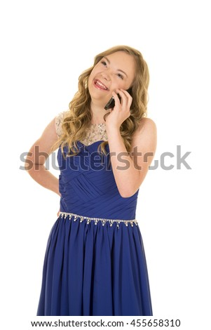 a woman with down syndrome in her fancy blue dress talking on her phone.