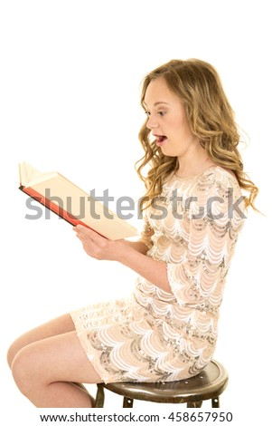 A woman with down syndrome sitting on a stool, reading a book with a shocked expression.