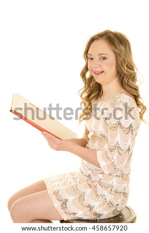 A woman with down syndrome sitting on a stool with a book and a big smile.