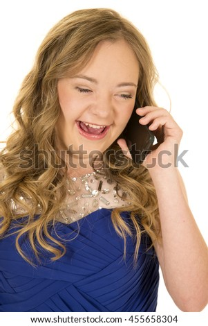 a  woman with down syndrome talking on her phone with a big smile on her face. - stock photo