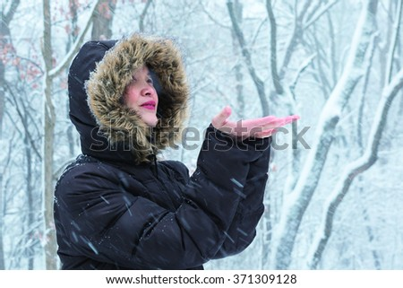 A woman with fur coat is having fun in blizzard
