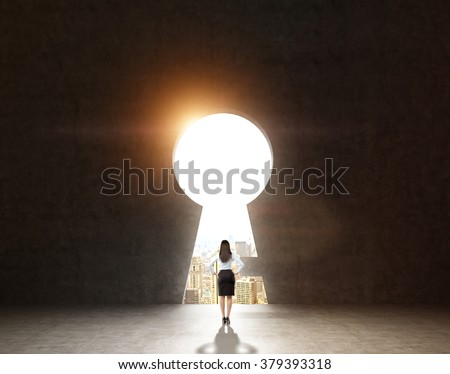 A woman with hands on hips standing in front of a huge keyhole, city and sky seen through it. Black background. Back view.  Concept of finding the way