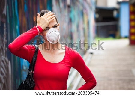 A woman with headache wearing a face mask in the city - stock photo
