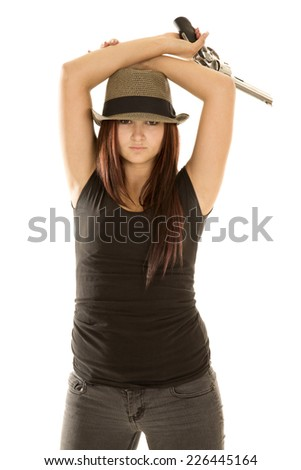 A woman with her arms on her head holding on to her pistol. - stock photo