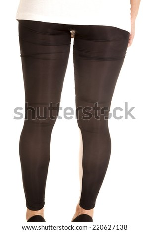 A woman with her back to the camera in her sheer leggings. - stock photo
