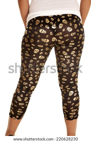 A woman with her back to the camera wearing black with gold skulls leggings. - stock photo