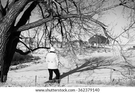 A woman with her back turned looking toward an abandoned farm yard in black and white rural landscape