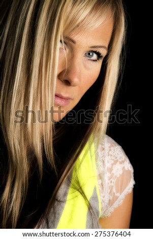 a woman with her eye covered looking through her hair with a serious expression. - stock photo